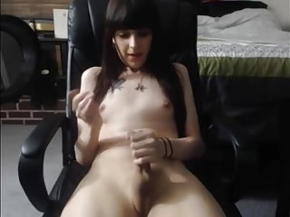Long-haired white T-girl stroking her shaved cock and cumming on cam